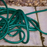 This photo of a garden hose with kinks illustrates the bottlenecks that impede workflow in the business office.