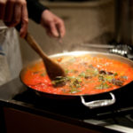 Motion blur photograph of chef stirring pasta sauce on stove.